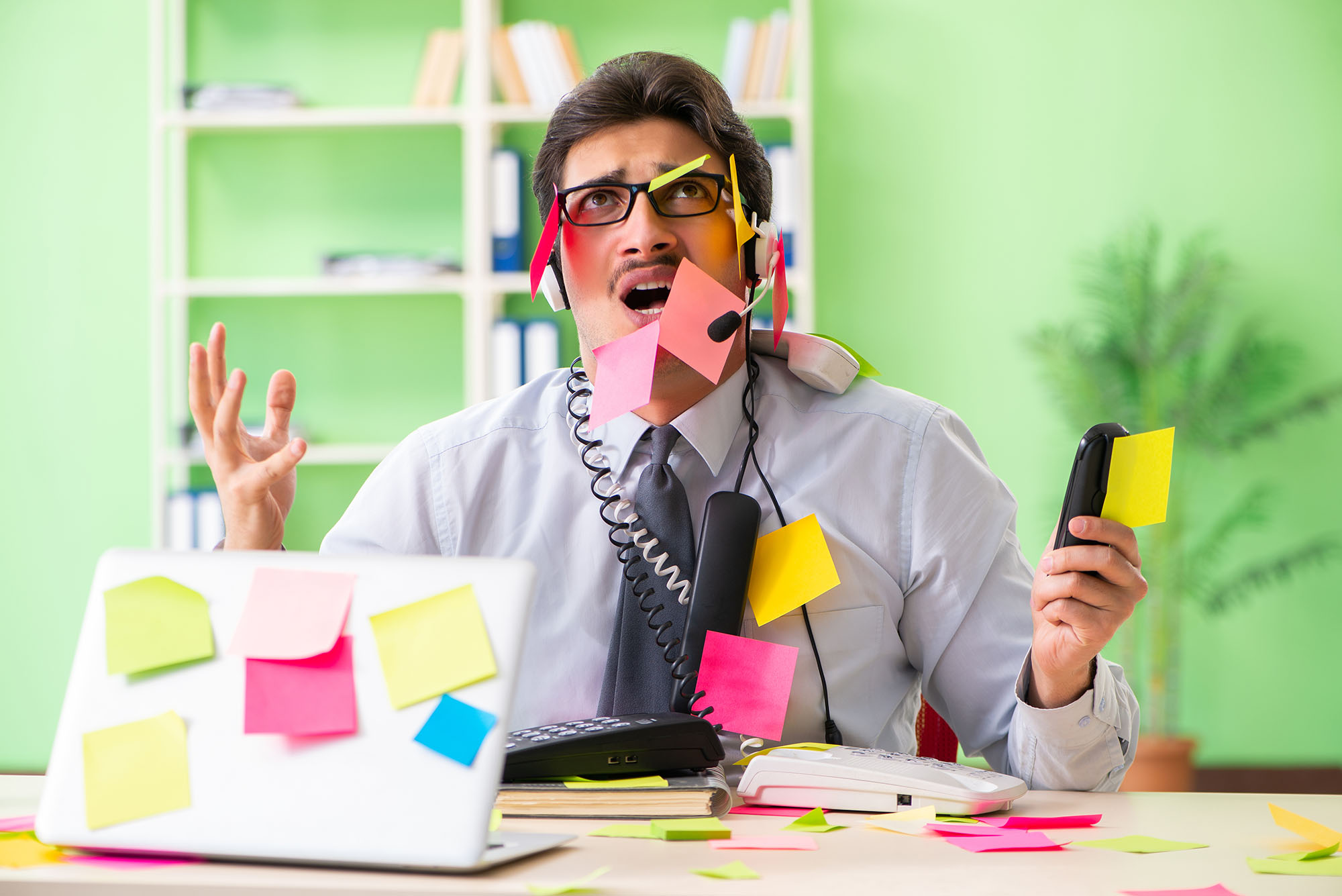 Man at IT service desk with post it notes and phones